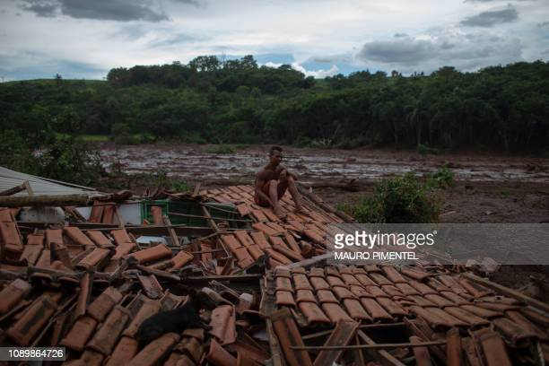 TOPSHOT Everything was shaking and I saw huge trees and people disappearing under the mud said Emerson dos Santos sitting on the roof of his family...