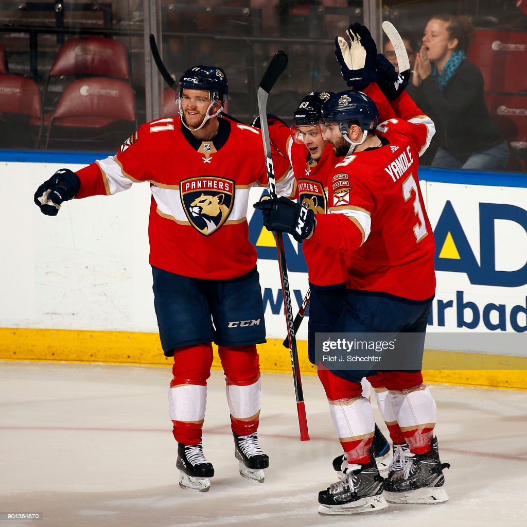 Evgeni Dadonov #63 of the Florida Panthers celebrates his second goal of the game with teammates Jonathan Huberdeau #11 and Keith Yandle #3 against the \Calgary Flames at the BB&T Center on January 12, 2018 in Sunrise, Florida.