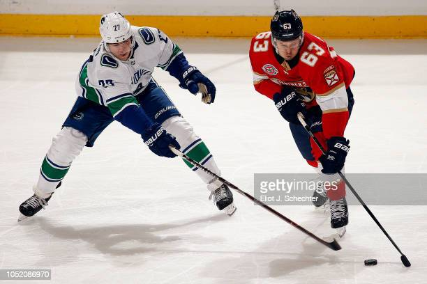 Evgeni Dadonov of the Florida Panthers skates with the puck against Ben Hutton of the Vancouver Canucks at the BBT Center on October 13 2018 in...