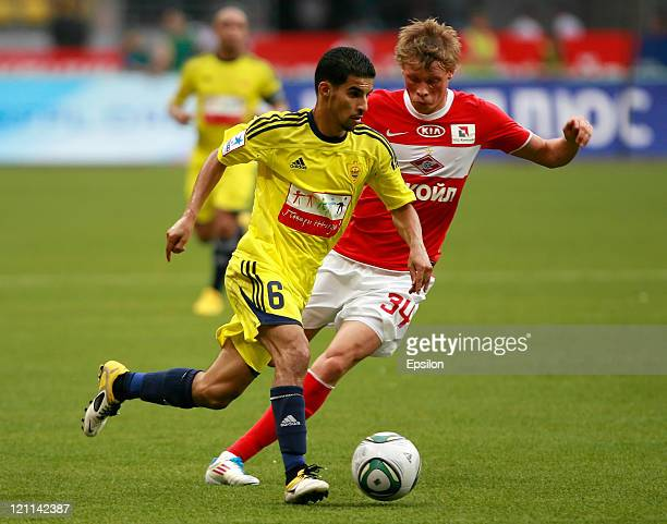 Evgeni Makeev of FC Spartak Moscow battles for the ball with Mbark Boussoufa of FC Anzhi Makhachkala during the Russian Football League Championship...