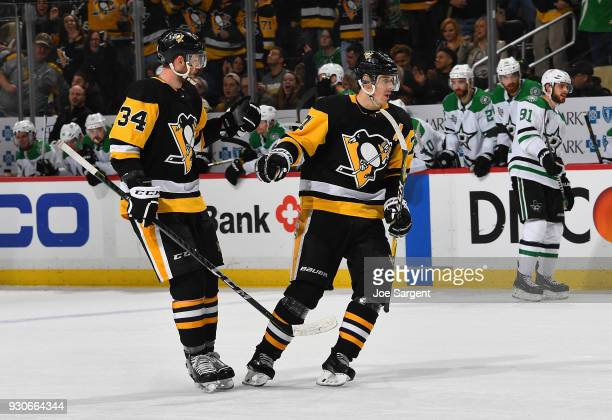 Evgeni Malkin celebrates his empty net goal with Tom Kuhnhackl of the Pittsburgh Penguins during the third period against the Dallas Stars at PPG...
