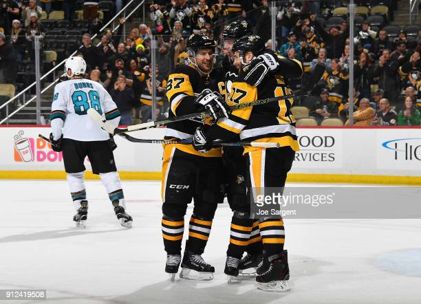 Evgeni Malkin celebrates his hat trick goal with Sidney Crosby and Bryan Rust of the Pittsburgh Penguins during the third period against the San Jose...