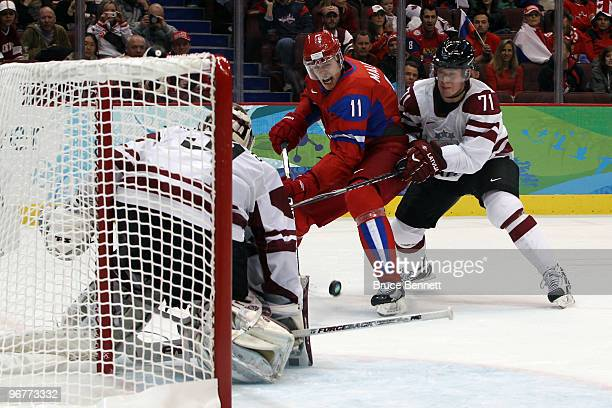Evgeni Malkin of Russia attempts a shot on goal under pressure from Georgijs Pujacs of Latvia during the ice hockey men's preliminary game between...