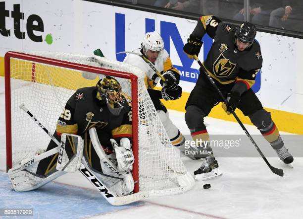 Evgeni Malkin of the Pittsburgh Penguins and Brayden McNabb of the Vegas Golden Knights battle for the puck behind MarcAndre Fleury of the Golden...