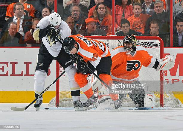 Evgeni Malkin of the Pittsburgh Penguins and Erik Gustafsson of the Philadelphia Flyers fight for the puck in front of Ilya Bryzgalov at the Wells...