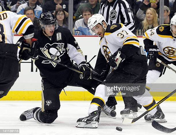 Evgeni Malkin of the Pittsburgh Penguins and Patrice Bergeron of the Boston Bruins battle for the faceoff during the game at Consol Energy Center on...