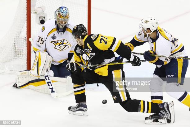 Evgeni Malkin of the Pittsburgh Penguins and Roman Josi of the Nashville Predators vie for the puck in front of Pekka Rinne during the second period...