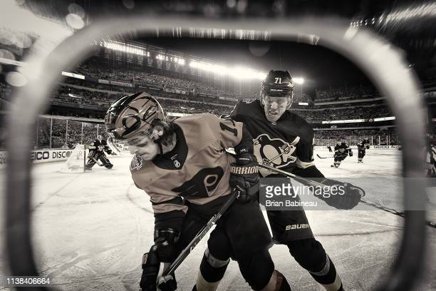 Evgeni Malkin of the Pittsburgh Penguins and Travis Konecny of the Philadelphia Flyers fight for the puck during the 2019 Coors Light NHL Stadium...
