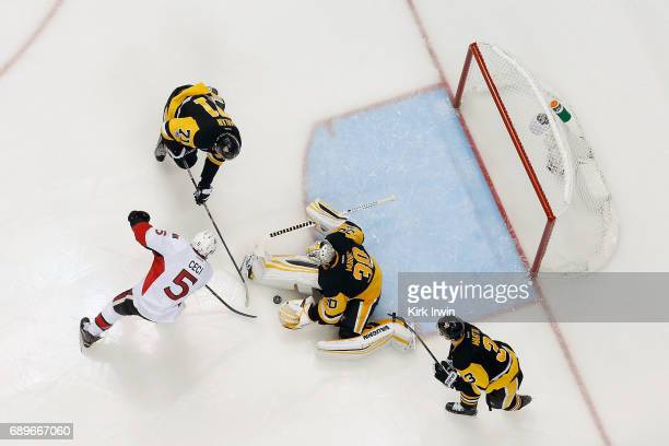 Evgeni Malkin of the Pittsburgh Penguins attempts to keep Cody Ceci of the Ottawa Senators from getting to the loose puck after Matt Murray of the...