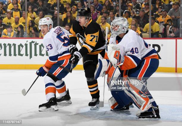 Evgeni Malkin of the Pittsburgh Penguins battles for position between Casey Cizikas and Robin Lehner of the New York Islanders in Game Three of the...
