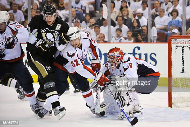 Evgeni Malkin of the Pittsburgh Penguins battles for position with Mike Green of the Washington Capitals in front of goaltender Simeon Varlamov of...