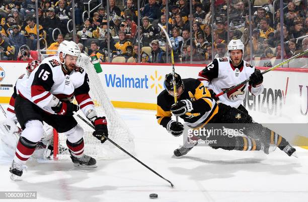 Evgeni Malkin of the Pittsburgh Penguins battles for the puck against Jordan Oesterle of the Arizona Coyotes and Brad Richardson of the Arizona...