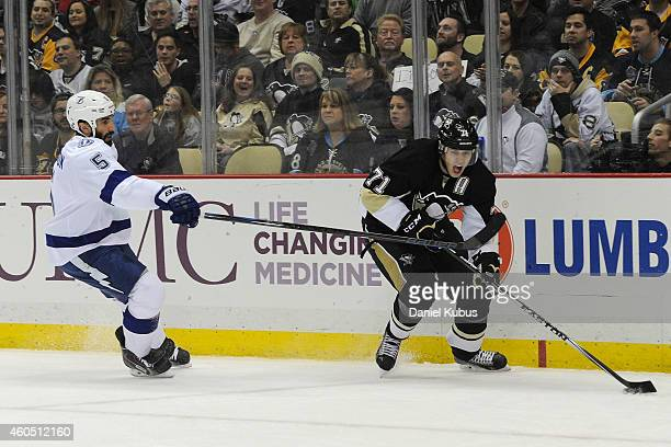Evgeni Malkin of the Pittsburgh Penguins carries the puck past Jason Garrison of the Tampa Bay Lightning at Consol Energy Center on December 15 2014...