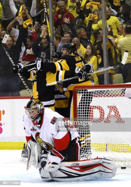 Evgeni Malkin of the Pittsburgh Penguins celebrates with his teammates Phil Kessel and Chris Kunitz after scoring a goal against Craig Anderson of...