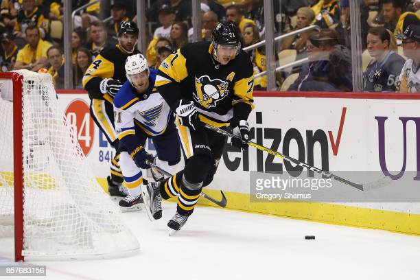 Evgeni Malkin of the Pittsburgh Penguins gains control of the puck in front of Vladimir Sobotka of the St Louis Blues during the third period at PPG...