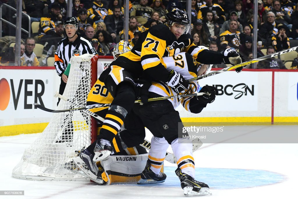 Evgeni Malkin #71 of the Pittsburgh Penguins gets caught on Patrice Bergeron's #37 back of the Boston Bruins at PPG PAINTS Arena on January 7, 2018 in Pittsburgh, Pennsylvania.