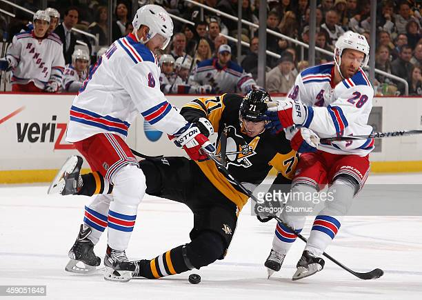 Evgeni Malkin of the Pittsburgh Penguins gets tripped up between Kevin Klein and Dominic Moore of the New York Rangers at Consol Energy Center on...