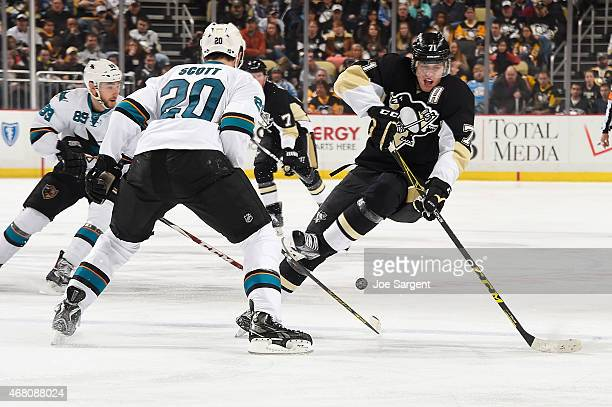 Evgeni Malkin of the Pittsburgh Penguins gets tripped up by John Scott of the San Jose Sharks at Consol Energy Center on March 29, 2015 in...