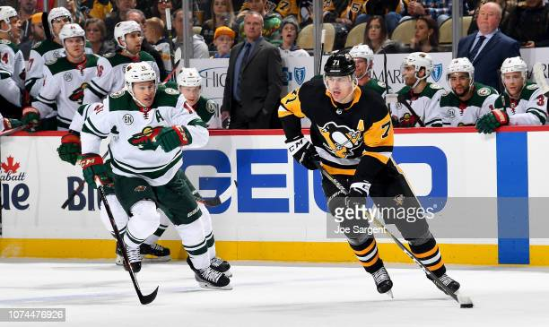 Evgeni Malkin of the Pittsburgh Penguins handles the puck against Zach Parise of the Minnesota Wild at PPG Paints Arena on December 20 2018 in...