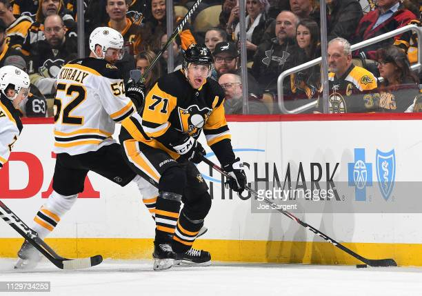 Evgeni Malkin of the Pittsburgh Penguins handles the puck against Sean Kuraly of the Boston Bruins at PPG Paints Arena on March 10 2019 in Pittsburgh...