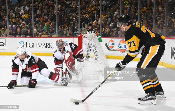 Evgeni Malkin of the Pittsburgh Penguins handles the puck against Antti Raanta of the Arizona Coyotes and Luke Schenn of the Arizona Coyotes at PPG...