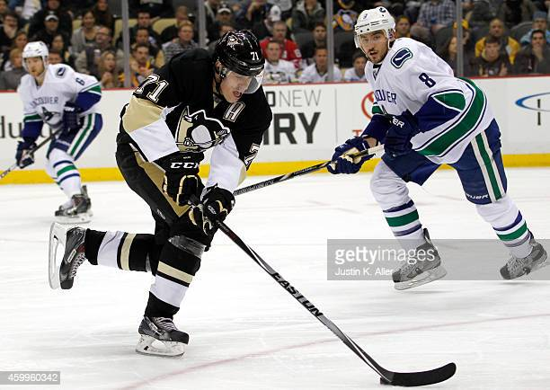 Evgeni Malkin of the Pittsburgh Penguins handles the puck in front of Chris Tanev of the Vancouver Canucks during the game at Consol Energy Center on...