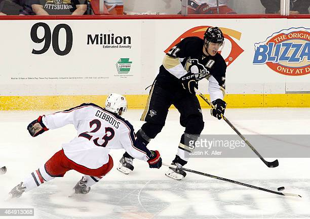 Evgeni Malkin of the Pittsburgh Penguins handles the puck in the third period against Brian Gibbons of the Columbus Blue Jackets during the game at...