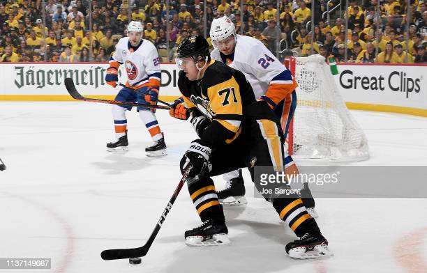 Evgeni Malkin of the Pittsburgh Penguins handles then puck in front of Scott Mayfield of the New York Islanders in Game Three of the Eastern...