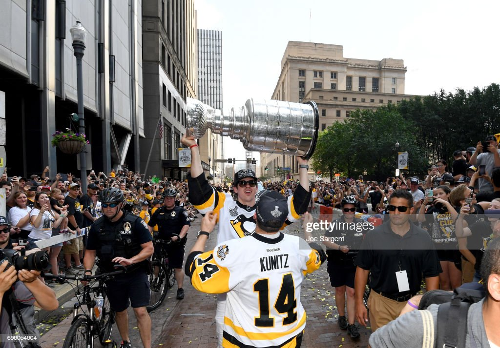 Evgeni Malkin #71 of the Pittsburgh Penguins hands the Stanley Cup to Chris Kunitz #14 during the Pittsburgh Penguins Victory Parade And Rally on June 14, 2017 in Pittsburgh, Pennsylvania.