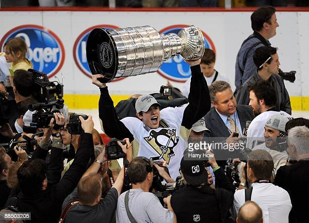 Evgeni Malkin of the Pittsburgh Penguins hoists the Stanley Cup overhead after Game Seven of the 2009 NHL Stanley Cup Finals against the Detroit Red...