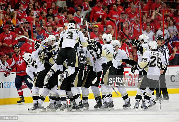 Evgeni Malkin of the Pittsburgh Penguins is mobbed by his teammates as they all celebrate Malkin's overtime winning goal over the Washington Capitals...