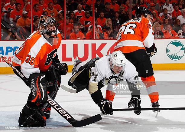 Evgeni Malkin of the Pittsburgh Penguins is sent flying by the stick of Erik Gustaffson of the Philadelphia Flyers as Flyers goalie Ilya Bryzgalov...