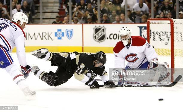 Evgeni Malkin of the Pittsburgh Penguins is taken down driving to the net between Michael Komisarek and Carey Price of the Montreal Canadiens on...
