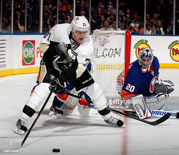 Evgeni Malkin of the Pittsburgh Penguins looks to pass the puck as Evgeni Nabokov of the New York Islanders defends his goal during the third period...