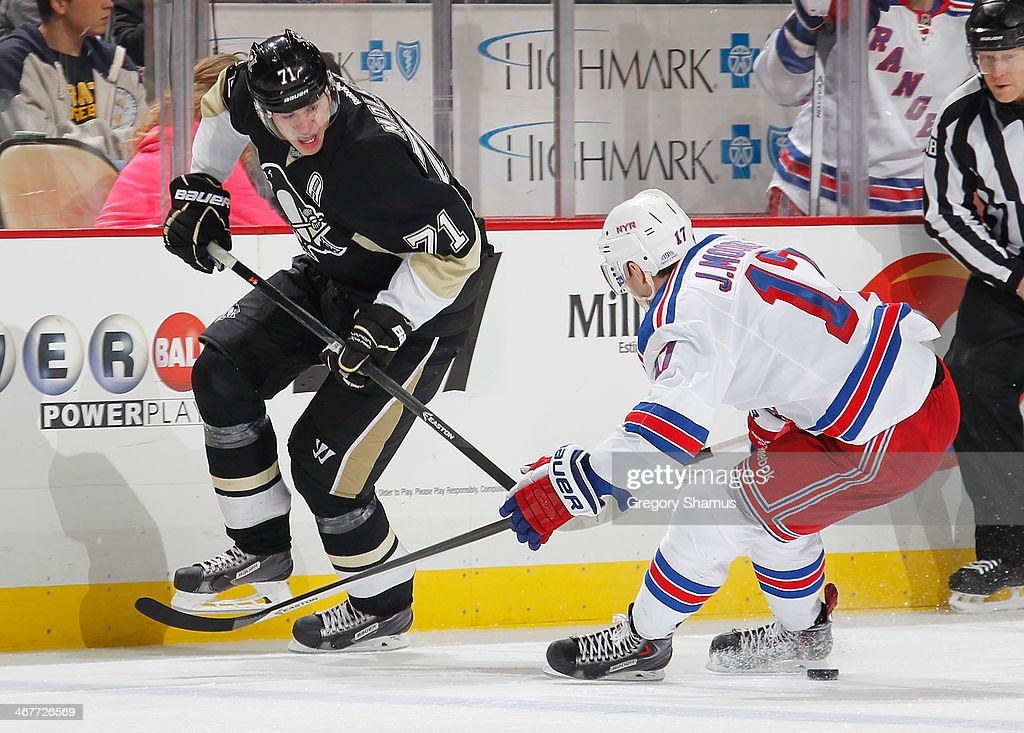 Evgeni Malkin #71 of the Pittsburgh Penguins makes a pass against John Moore #17 of the New York Rangers on February 7, 2014 at Consol Energy Center in Pittsburgh, Pennsylvania. New York won the game 4-3 in a shootout.