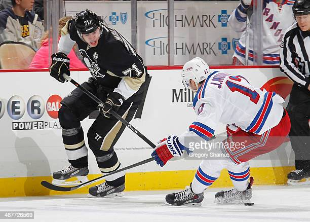 Evgeni Malkin of the Pittsburgh Penguins makes a pass against John Moore of the New York Rangers on February 7, 2014 at Consol Energy Center in...