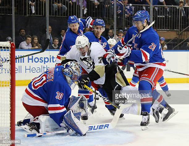 Evgeni Malkin of the Pittsburgh Penguins moves in on Henrik Lundqvist of the New York Rangers and is tripped up during the first period in Game Three...