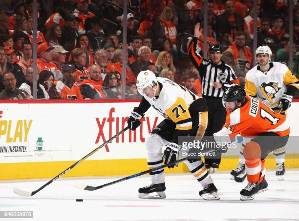 Evgeni Malkin of the Pittsburgh Penguins moves the puck ahead of Sean Couturier of the Philadelphia Flyers during the third period in Game Three of...