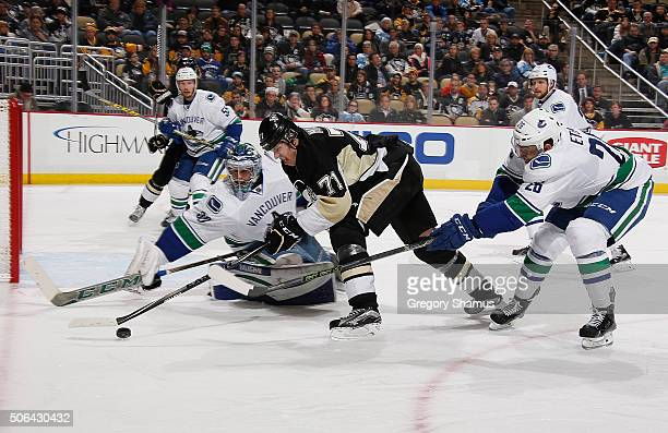 Evgeni Malkin of the Pittsburgh Penguins moves the puck between the defense of Ryan Miller and Emerson Etem of the Vancouver Canucks at Consol Energy...