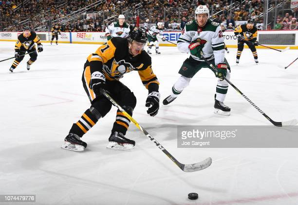 Evgeni Malkin of the Pittsburgh Penguins moves the puck in front of Jonas Brodin of the Minnesota Wild at PPG Paints Arena on December 20 2018 in...