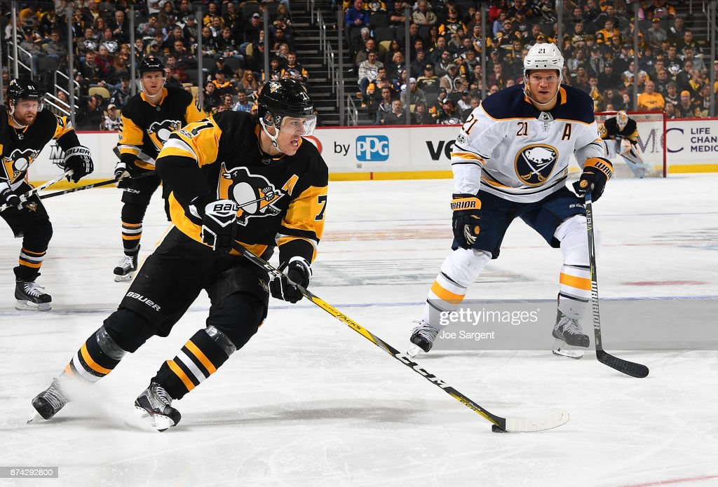 Evgeni Malkin #71 of the Pittsburgh Penguins moves the puck in front of Kyle Okposo #21 of the Buffalo Sabres at PPG Paints Arena on November 14, 2017 in Pittsburgh, Pennsylvania.
