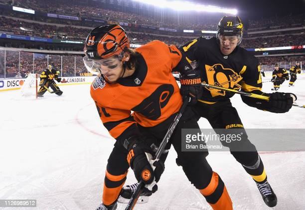 Evgeni Malkin of the Pittsburgh Penguins pursues the play of Travis Konecny of the Philadelphia Flyers during the 2019 Coors Light NHL Stadium Series...