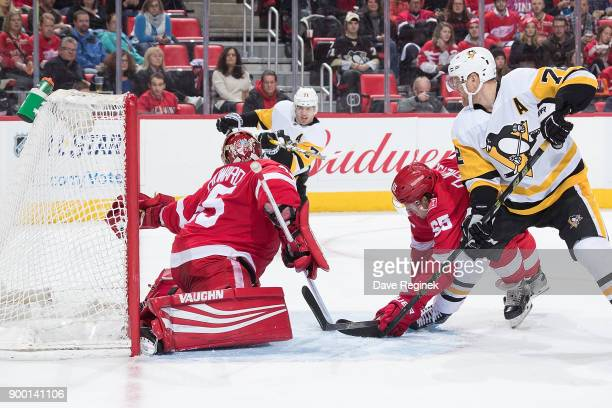Evgeni Malkin of the Pittsburgh Penguins puts the puck into goaltender Jimmy Howard of the Detroit Red Wings glove and scores a second period goal as...