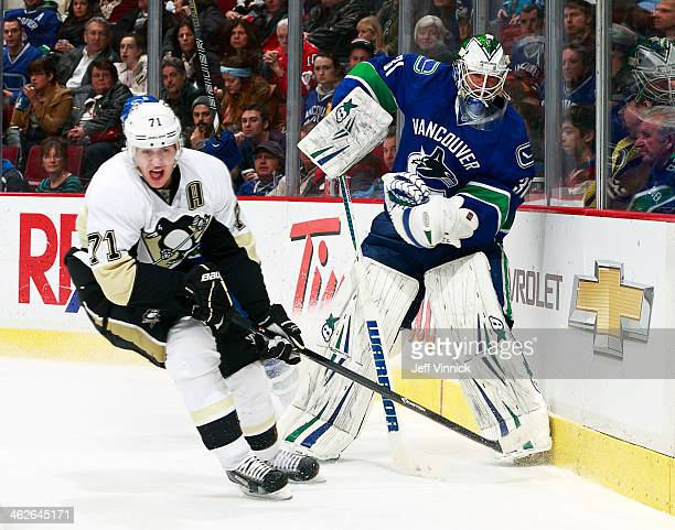 Evgeni Malkin of the Pittsburgh Penguins skates by as Eddie Lack of the Vancouver Canucks shoots the puck during their NHL game at Rogers Arena...