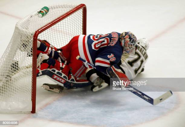 Evgeni Malkin of the Pittsburgh Penguins slides into goaltender Henrik Lundqvist of the New York Rangers after a break away attempt on goal that...