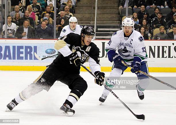 Evgeni Malkin of the Pittsburgh Penguins takes a shot in front of Henrik Sedin of the Vancouver Canucks in the first period during the game at Consol...