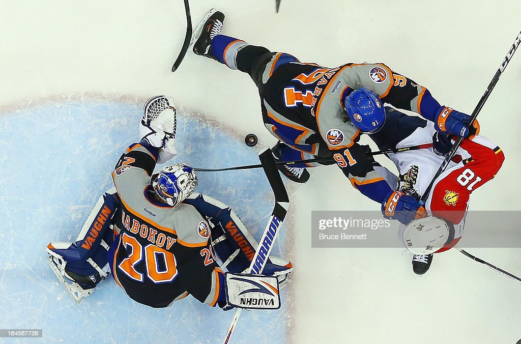 Evgeni Nabokov #20 of the New York Islanders and John Tavares #91 defend the net against Shawn Matthias #18 of the Florida Panthers at the Nassau Veterans Memorial Coliseum on March 24, 2013 in Uniondale, New York. The Islanders defeated the Panthers 3-0.