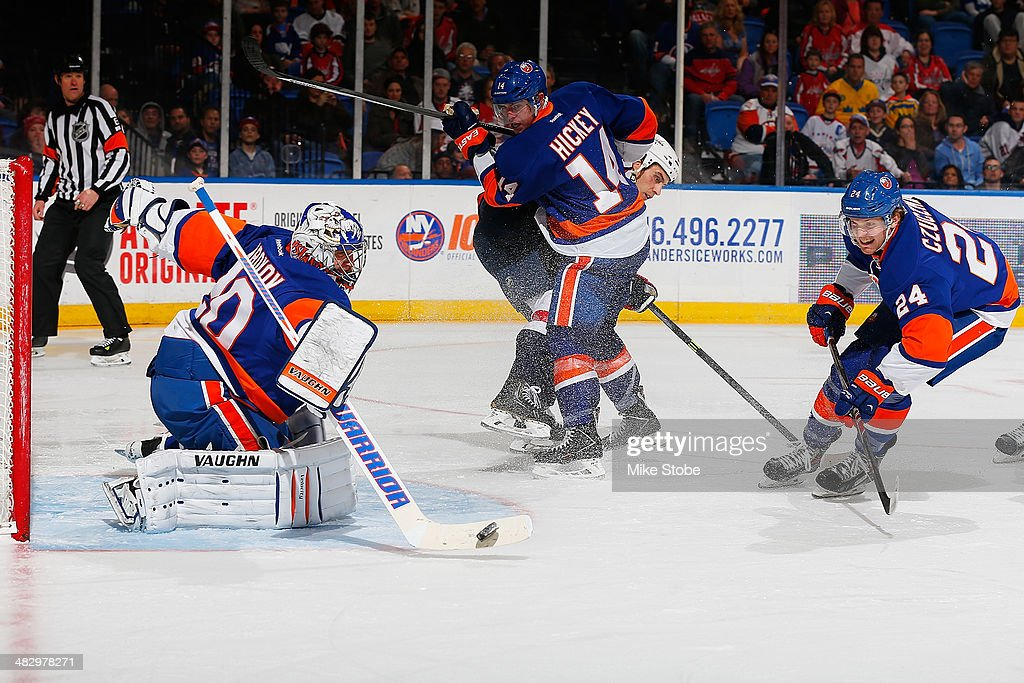 Evgeni Nabokov #20 of the New York Islanders clears the puck away from the net as teammates Kevin Czuczman #24 and Thomas Hickey #14 look on against the Washington Capitals at Nassau Veterans Memorial Coliseum on April 5, 2014 in Uniondale, New York. The Capitals defeated the Islanders 4-3.
