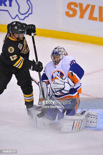 Evgeni Nabokov of the New York Islanders deflects the puck against Jarome Iginla of the Boston Bruins at the TD Garden on December 31 2013 in Boston...
