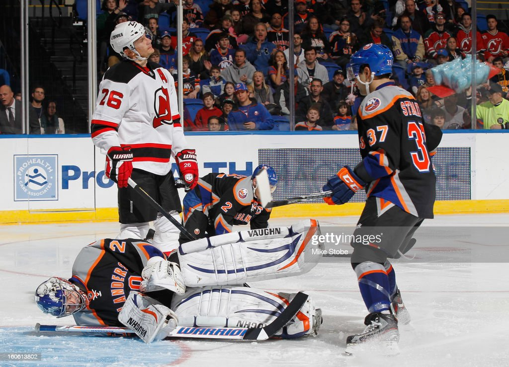 Evgeni Nabokov #20 of the New York Islanders falls to the ice in front of Patrik Elias #26 of the New Jersey Devils at Nassau Veterans Memorial Coliseum on February 3, 2013 in Uniondale, New York. The Devils defeated the Islanders 3-0